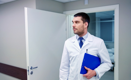 clinic, profession, people, health care and medicine concept - doctor with clipboard at hospital corridor Stock Photo
