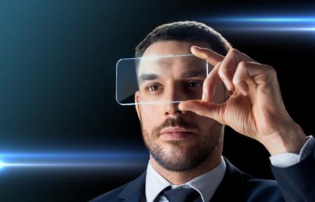 비즈니스, 증강 현실과 미래의 기술 개념 - 검정 배경 위에 투명한 스마트 폰으로 작업하는 양복 사업가 스톡 콘텐츠