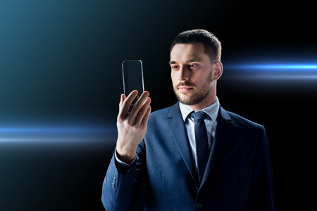 business, augmented reality and future technology concept - businessman in suit working with transparent smartphone over black background