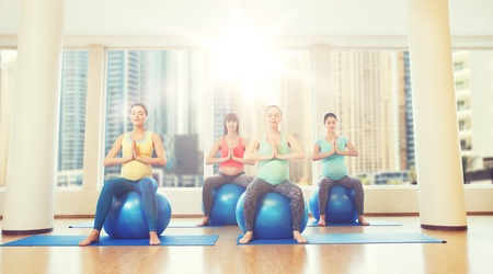 pregnancy, sport, fitness, people and healthy lifestyle concept - group of happy pregnant women exercising on ball in gym over city window view background Stock Photo