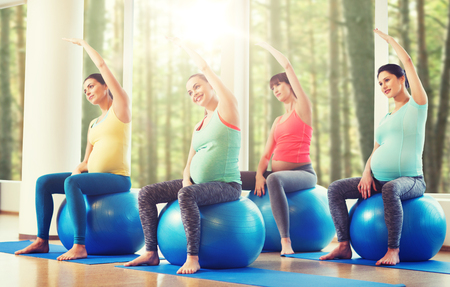 fitball: pregnancy, sport, fitness, people and healthy lifestyle concept - group of happy pregnant women exercising on ball in gym