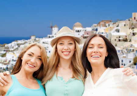 travel, tourism and summer vacation concept - group of happy smiling women or friends over oia town on santorini island background Stock Photo