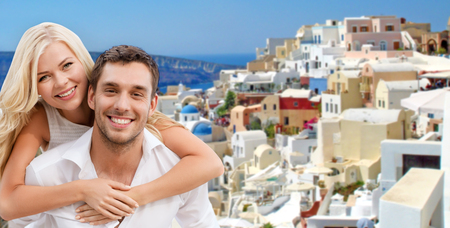 travel, tourism and summer holidays concept - happy couple hugging over santorini island background