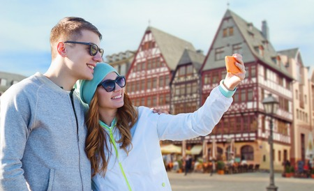 tourism, travel and people concept - smiling couple with smartphone taking selfie over frankfurt am main city street background