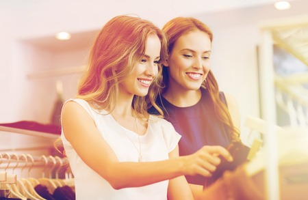sale, consumerism and people concept - happy young women with shopping bags choosing clothes at clothing shop Stock Photo