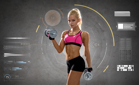 fitness, sport, people and training concept - happy young sporty woman exercising with heavy steel dumbbells over gray concrete background