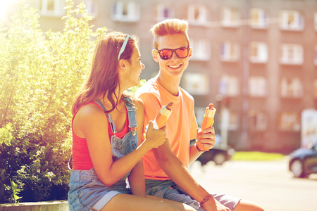fast food, summer and people concept - happy teenage couple eating hot dogs sitting on city street bench Imagens