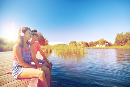 holidays, vacation, love and people concept - happy teenage couple with earphones sitting on river berth and listening to music at summer Imagens - 81895662