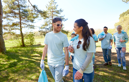 volunteering, charity, people and ecology concept - happy young volunteers with garbage bags talking outdoors Stock Photo