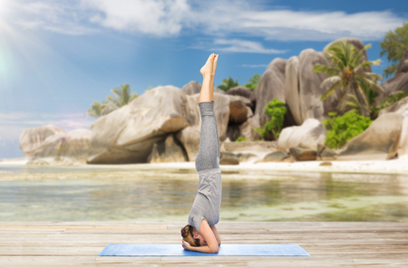 fitness, sport and people concept - woman doing yoga in headstand pose on mat over exotic tropical beach background