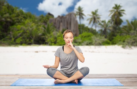 fitness, meditation and healthy lifestyle concept - woman doing yoga breathing exercise in lotus pose on mat over exotic tropical beach background Banque d'images