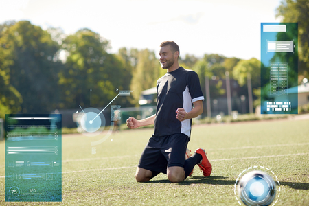sport, technology, success and people concept - happy soccer player with on football field Banco de Imagens