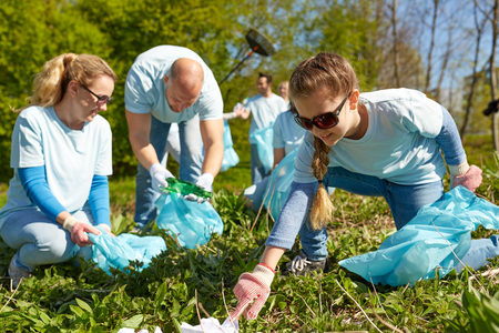 selfless: volunteering, charity, people and ecology concept - group of happy volunteers with garbage bags cleaning area in park Stock Photo