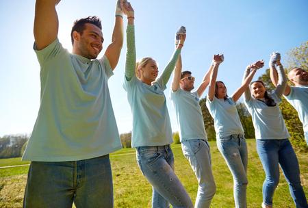 ボランティア、慈善団体、人々 の概念 - 屋外手を取り合って幸せなボランティアのグループ