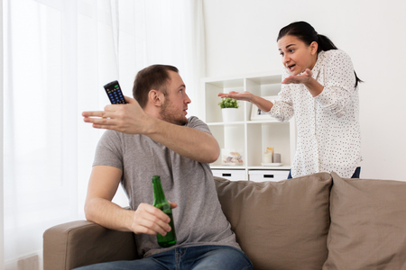people, relationship difficulties, conflict and family concept - angry woman having argument with man drinking beer and watching tv at home