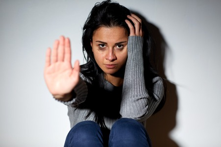 people, grief and domestic violence concept - unhappy woman sitting on floor and crying at home