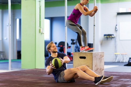 피트 니스, 스포츠, 훈련, 운동 및 사람들이 개념 - 행복 한 여자와 남자 의학 공을 곱슬 하 고 상자를 하 고 체육관에서 점프 스톡 콘텐츠