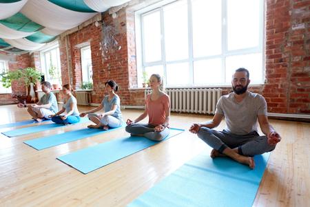 Fitness, yoga y concepto de estilo de vida saludable - grupo de personas meditando en posición de loto en el estudio Foto de archivo - 81896097