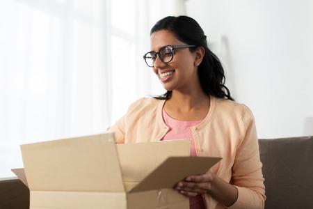 사람, 배달, 운송 및 우편 서비스 개념 - 행복 한 젊은 인도 여자 열기 골 판지 상자 또는 소포 집에서 스톡 콘텐츠