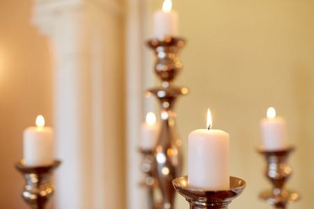 ministration: religion concept - candles burning in church