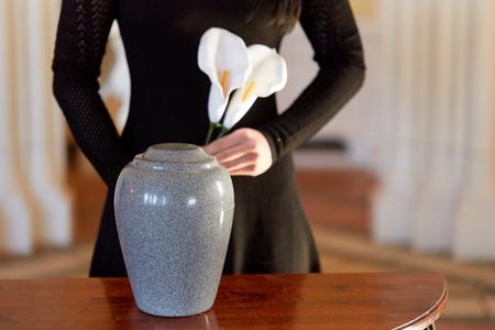 crematie, mensen en rouw concept - vrouw met bloemen en cinerary urn op begrafenis in de kerk