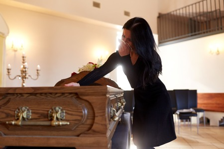 people and mourning concept - crying woman with coffin at funeral in church