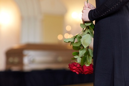 people and mourning concept - close up of woman with red roses and coffin at funeral in church Imagens