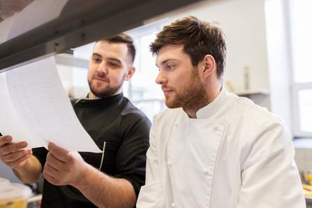 요리 음식, 직업과 사람들이 개념 - 행복 남성 요리사 및 식료품 목록 또는 레스토랑 주방에서 청구서와 요리 스톡 콘텐츠