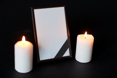begrafenis en rouw concept - leeg fotokader met lint en brandende kaarsen op zwarte achtergrond
