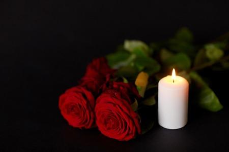 Beerdigung und Trauer-Konzept - rote Rosen und brennende Kerze auf schwarzem Hintergrund