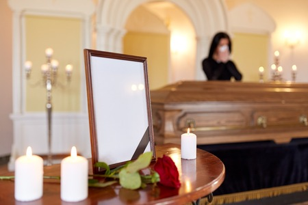 people and mourning concept - photo frame with black ribbon, candles and woman crying near coffin at funeral in church Stock Photo