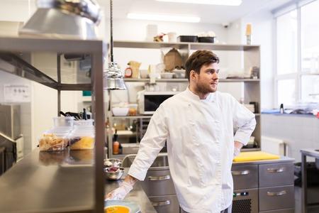Concetto di cucina, professione e persone di cibo - cuoco maschio felice cuoco con piatto di zuppa e insalata al tavolo della cucina del ristorante Archivio Fotografico - 81896623