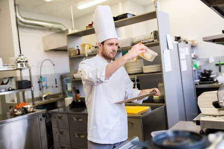 cooking, profession and people concept - male chef cook with clipboard doing inventory in restaurant kitchen