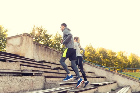 fitness, sport, exercising and lifestyle concept - couple running upstairs on stadium Reklamní fotografie