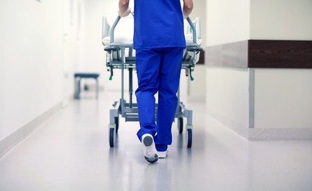 people, healthcare, reanimation and medicine concept - nurse carrying hospital gurney to emergency room