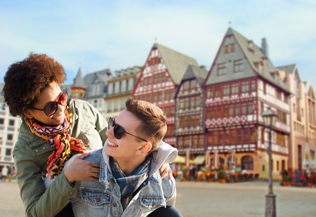 tourism, travel and people concept - happy teenage couple in shades having fun over frankfurt am main city street background Imagens