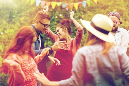happy friends dancing at summer party in garden Stock Photo