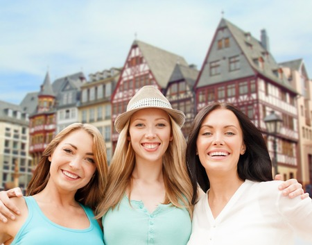 travel, tourism and summer vacation concept - group of happy smiling women or friends over frankfurt am main city background