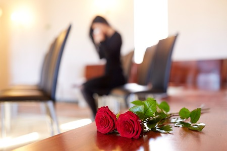 red roses and woman crying at funeral in church Stock Photo