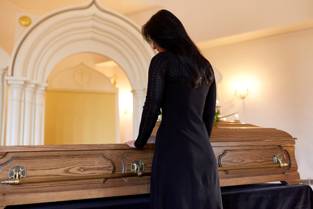 people and mourning concept - sad woman with coffin at funeral in orthodox church