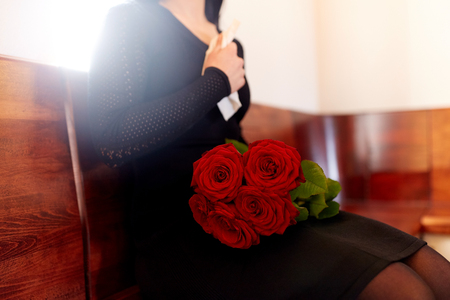 people, grief and mourning concept - close up of woman with red roses sitting on bench at funeral in church Stock Photo