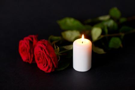 begrafenis en rouw concept - rode rozen en brandende kaars op zwarte achtergrond