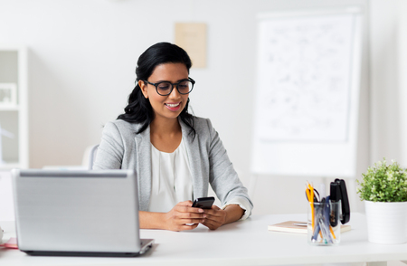 business, technology, communication and people concept - happy smiling businesswoman with smartphone and laptop at office Stock Photo