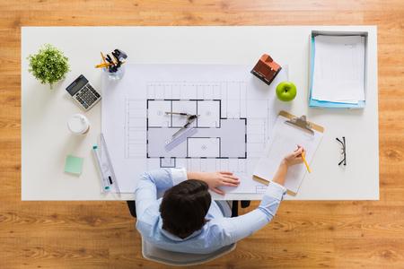Architect met blauwdruk schrijven naar klembord