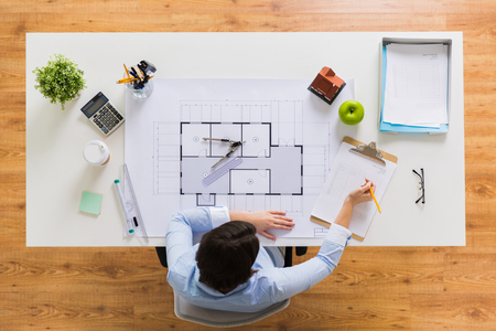 architect with blueprint writing to clipboard Stock Photo