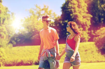 happy teenage couple walking at summer park Imagens