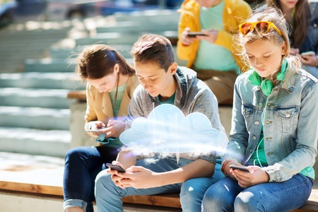 teenage friends with smartphones outdoors