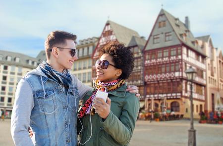 couple with smartphone and earphones in frankfurt