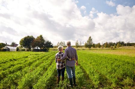 landbouw, tuinieren, landbouw en mensenconcept - gelukkig hoger paar bij de zomerlandbouwbedrijf