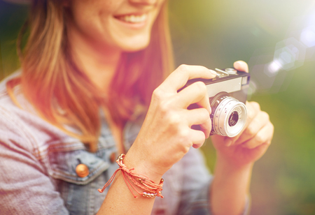 photography and people concept - close up of young woman with film camera photographing outdoors
